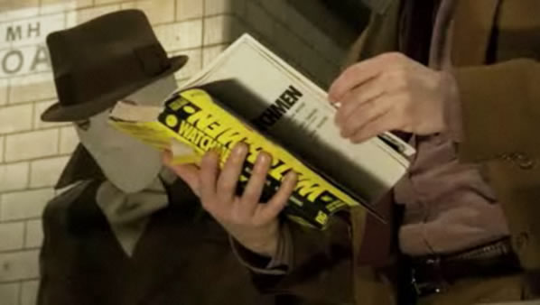 Partick Wilson reads Watchmen on set with Jackie Earle Haley in costume behind him.